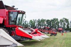 Трактор современного техника красный вспахивая зеленое аграрное поле весной на ферме Пшеница засева жатки Стоковые Изображения