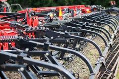 Трактор современного техника красный вспахивая зеленое аграрное поле весной на ферме Пшеница засева жатки Стоковое фото RF