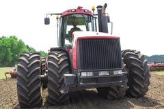 Трактор современного техника красный вспахивая зеленое аграрное поле весной на ферме Пшеница засева жатки Стоковая Фотография