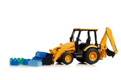 Трактор с игрушками кирпича, белая предпосылка Backhoe стоковые фото