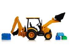 Трактор с игрушками кирпича, белая предпосылка Backhoe стоковое фото rf