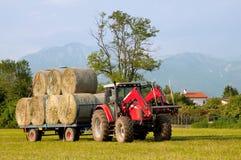 Трактор с курганом bales сена Стоковые Изображения