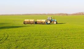 Трактор с прикрепленным аграрным оборудованием делает поворот на поле стоковые фотографии rf