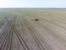 Трактор с прикрепленной на петлях системой распыляя пестицидов Удабривающ с трактором, в форме аэрозоля, на поле зимы w Стоковое Изображение