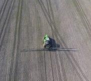 Трактор с прикрепленной на петлях системой распыляя пестицидов Удабривающ с трактором, в форме аэрозоля, на поле зимы w Стоковые Фото