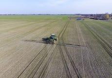 Трактор с прикрепленной на петлях системой распыляя пестицидов Удабривающ с трактором, в форме аэрозоля, на поле зимы w Стоковая Фотография RF