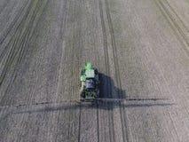 Трактор с прикрепленной на петлях системой распыляя пестицидов Удабривающ с трактором, в форме аэрозоля, на поле зимы w Стоковая Фотография