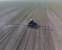 Трактор с прикрепленной на петлях системой распыляя пестицидов Удабривающ с трактором, в форме аэрозоля, на поле зимы w Стоковые Фотографии RF