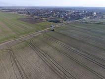Трактор с прикрепленной на петлях системой распыляя пестицидов Удабривающ с трактором, в форме аэрозоля, на поле зимы w Стоковое Изображение RF