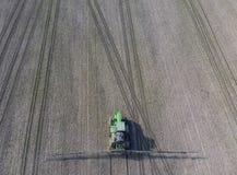 Трактор с прикрепленной на петлях системой распыляя пестицидов Удабривающ с трактором, в форме аэрозоля, на поле зимы w Стоковое фото RF