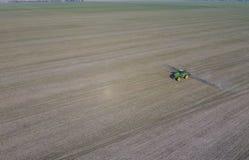 Трактор с прикрепленной на петлях системой распыляя пестицидов Удабривающ с трактором, в форме аэрозоля, на поле зимы w Стоковое Фото