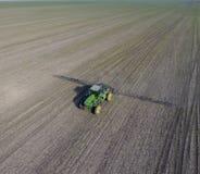 Трактор с прикрепленной на петлях системой распыляя пестицидов Удабривающ с трактором, в форме аэрозоля, на поле зимы w Стоковые Изображения