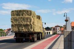 Трактор с трейлером нагрузил с брикетами сена Стоковое Фото
