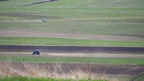 Трактор управляет через поле в горах видеоматериал
