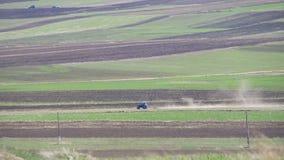 Трактор управляет через поле в горах сток-видео