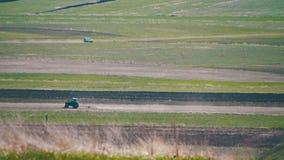 Трактор управляет через поле в горах акции видеоматериалы