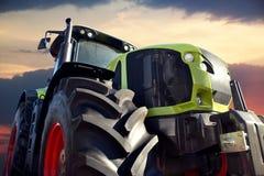 Трактор фермы работая на заходе солнца Стоковые Изображения RF