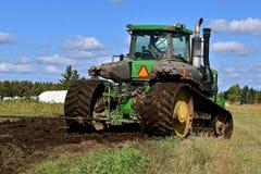 Трактор John Deere вытягивая машинное оборудование в грязи стоковые изображения