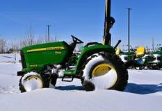 Трактор John Deere 3025E покрытый снегом Стоковые Фото