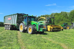 Трактор John Deere 8335R колеса при трейлер и корм жать зернокомбайн John Deere 7450 Стоковые Фотографии RF