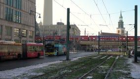 Трамваи, шины, движение и пассажиры и поезд покидая станция Alexanderplatz, Берлин, Германия сток-видео