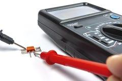 Транзистор теста используя портативное всеобщее электронное устройство стоковые фото