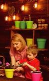 Трансплантируя концепция Цветок матери и сына трансплантируя в новом баке Комнатное растение матери и ребенка трансплантируя внут стоковое изображение