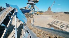 Транспортер двигает щебень пока сортирующ его Работа горного оборудования видеоматериал