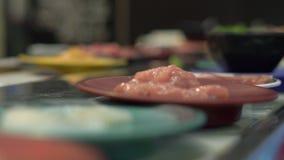 Транспортер еды Азиатское кафе стиля с едой двигая дальше транспортер в маленькие плиты Концепция расточительствовать еды расточи видеоматериал
