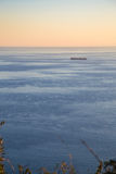 Транспортное судно на заходе солнца Стоковые Изображения RF