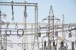 Трансформаторы высокого напряжения и поддержки линии электропередач Голубое небо без облаков добросердечная станция реки силы Стоковое фото RF