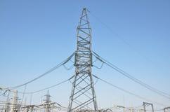 Трансформаторы высокого напряжения и поддержки линии электропередач Голубое небо без облаков добросердечная станция реки силы Стоковые Изображения RF