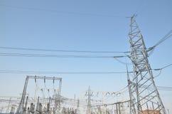 Трансформаторы высокого напряжения и поддержки линии электропередач Голубое небо без облаков добросердечная станция реки силы Стоковые Фото