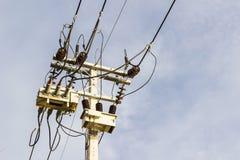 Трансформаторы электрического столба против twilight предпосылки голубого неба Стоковое Фото
