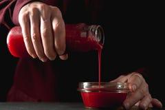 Трансфузия соуса клюквы от бутылки в шар Стоковые Изображения RF