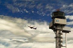 Трасса земл-небо Пассажирский самолет принимает на фоне облачного неба и башни управления полетом на стоковое фото rf