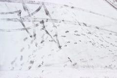 Трассировки автошин и следы ноги подошвы ботинка на снеге Стоковое Изображение RF