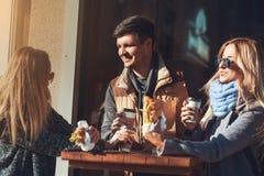 Тратить время с друзьями Группа в составе жизнерадостное молодые люди говоря друг к другу пока ел круассан и сандвичи Стоковая Фотография