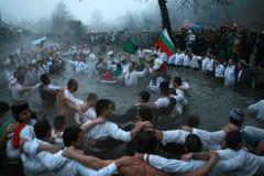 Традиции явления божества - Джордан Люди танцуют в ледистых водах реки Tunja 6-ого января 2011, Kalofer, Болгария Стоковые Изображения RF