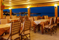 Традиционное европейское кафе в ноче на острове ночи Крита Греции Деревянные стулья с белыми скатертями на заливе стоковое фото
