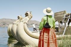 Традиционно одетая женщина Aymara смотря лодочника достигая к ей, Titi плавая островов Uros, озера стоковые фото