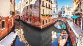 Традиционные гондолы на узком канале между красочными историческими домами в Венеции Италии Стоковое Изображение
