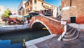 Традиционные гондолы на узком канале между красочными историческими домами в Венеции Италии Стоковое Фото