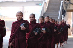 Традиционные милостыни давая церемонию распределяя еды к буддийским монахам на улицах Янгона, Мьянмы Стоковые Изображения RF