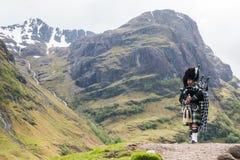 Традиционный волынщик в шотландских гористых местностях стоковая фотография rf