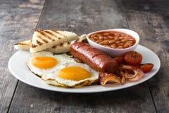 Традиционный польностью английский завтрак с яичницами, сосисками, фасолями, грибами, зажарил томаты и бекон Стоковые Фото