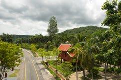 Традиционный тайский дом потерял в сочной растительности деревьев в парке Стоковое Изображение