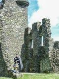 Традиционный шотландский волынщик на руинах замка Kilchurn стоковые изображения