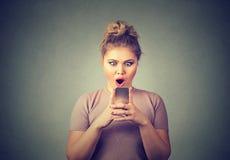 Тревоженая изумленная девушка смотря телефон видя плохую новость с отвратительной эмоцией на стороне Стоковое Изображение RF