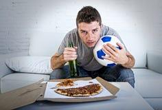 Тревоженая молодого человека шальная и слабонервная смотря футбольная игра на кресле телевидения дома Стоковые Фотографии RF